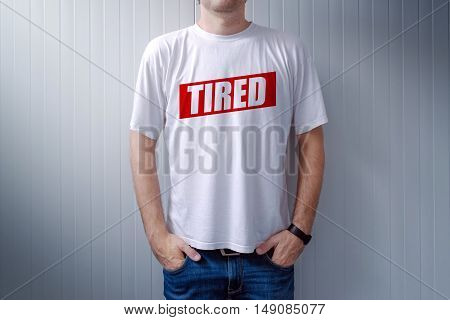 Guy wearing white t-shirt with label Tired printed on chest text is added in post production