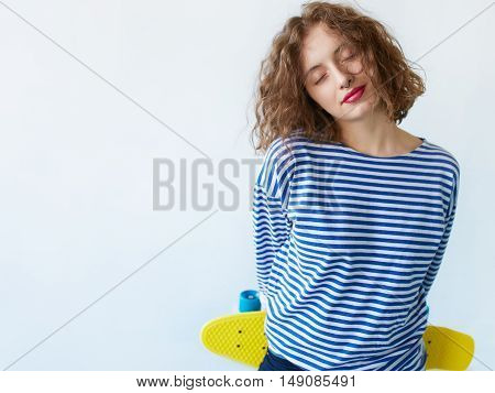 Close up Thoughtful Smiling brunette Girl with curly hair Closing her Eyes While Leaning on a White Wall with Copy Space