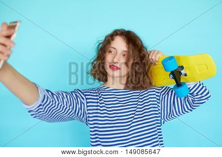 Fashion and technology concept - stylish young girl in casual clothes with skateboard makes self-portrait on the smartphone isolated on the blue wall