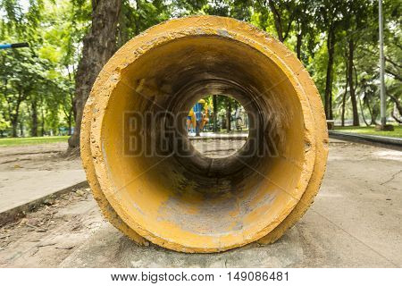 yellow concrete pipe as tunnel of playground in Lumpini park Bangkok Thailand