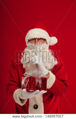 christmas Photo of kind Santa Claus giving xmas present and looking at camera. secret hand and lips