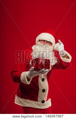 christmas Photo of kind Santa Claus giving xmas present and looking at camera