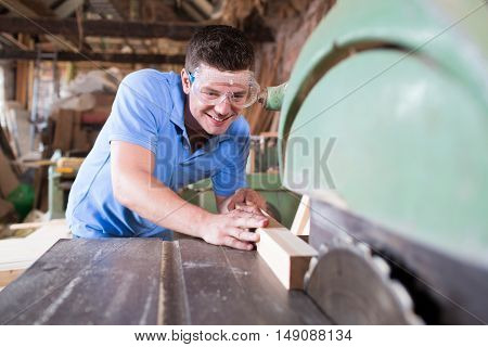 CarpenterWearing safety Goggles Cutting Wood On Circular Saw