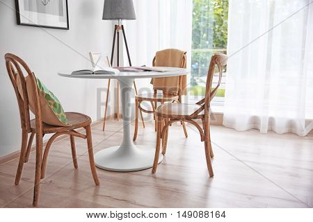Modern white table and wooden chairs near window