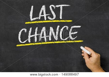 Last chance written on a dark blackboard