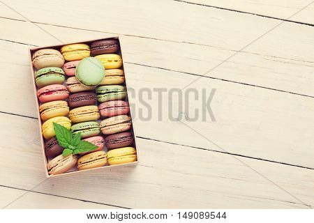 Colorful macaroons on wooden table. Sweet macarons in gift box. Top view with copy space for your text. Retro toned