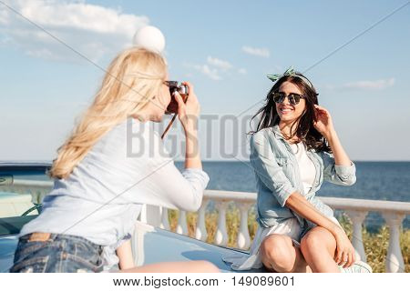 Cheerful attractive young woman sitting and posing to girl photographer in summer