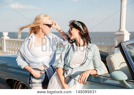 Two happy pretty young women standing and talking near cabriolet