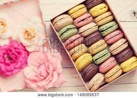 Colorful macaroons and rose flowers on wooden table. Sweet macarons in gift box. Top view. Retro toned
