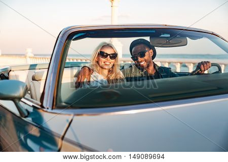 Happy young couple in sunglasses driving cadriolet