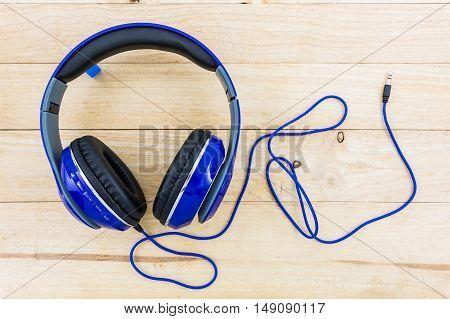 Blue headphones on the wood desk background.