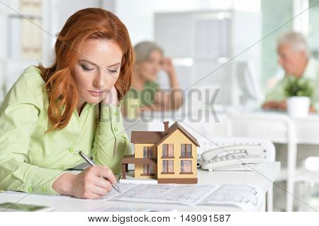 Portrait Of working Female house agent and business people In Office