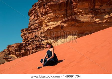 Photo of the Stylish girl sitting on red dune relaxing and enjoying vacation retreat. Inspiration, travel mental health concept