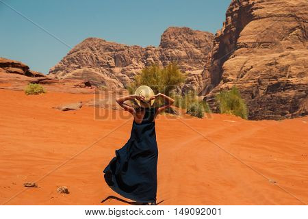 Photo of the Stylish girl wearing trendy hat and long dress enjoying life, amazing landscape. Inspiration, freedom travel, luxury vacation, active life concept.