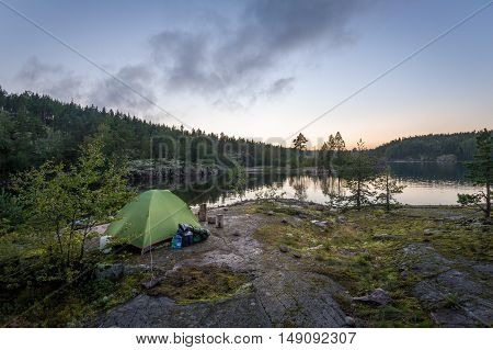 Late evening landscape view of Ladoga lake islands and small tourist tent on the rocks. Karelia, Russia.