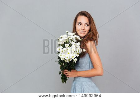 Portrait of happy pretty young woman with bouquet of flowers over grey background
