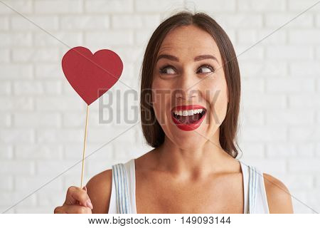 Happy beautiful woman holding red paper heart and look it, white brick wall on background