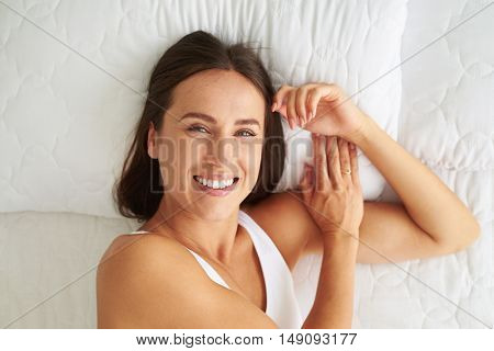 Close-up of Caucasian young  positive woman who's face displaying joy while lying in the bed
