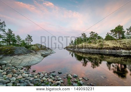 Ladoga lake bay with sunset clouds reflected on the water. Stunning nature of Karelia republic, Russia.
