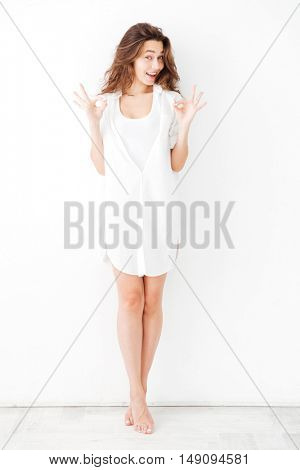 Charming playful young girl in white shirt showing okay gesture isolated on a white background