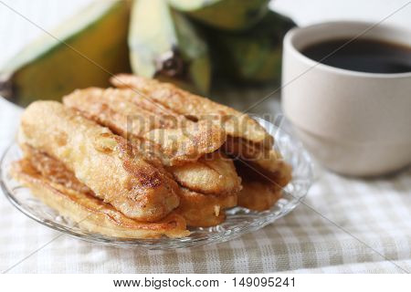 Banana fritters and coffee served on table