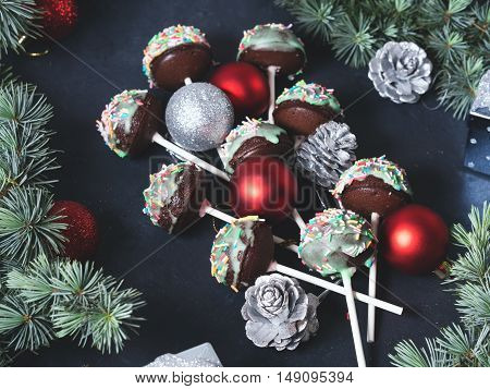 Christmas tree branches with baubles and cake pops tree with colored sprinkles on green frosting on dark black concrete effect background