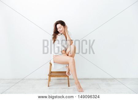 Portrait of a lovely young woman posing on the chair isolated on a white background