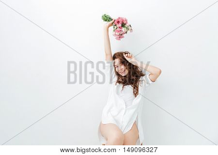 Portrait of a cute happy woman in casual clothes holding flowers over white background