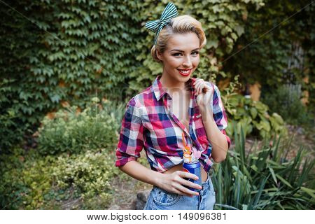 Cheerful beautiful young woman walking in the garden and drinking soda