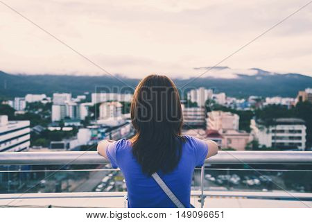 Hipster young girl looking the city on observation deck Vintage tone