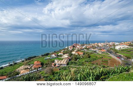 Typical Madeira island rural landscape with small houses, farms and Atlantic ocean water. Madeira island, Portugal.
