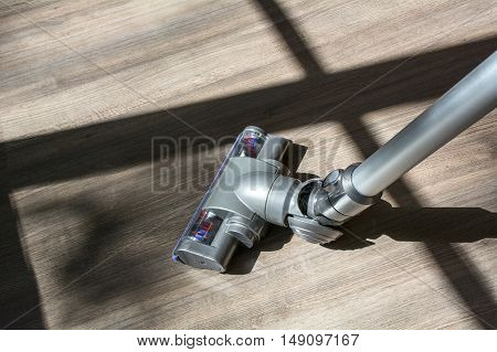 A vacuum cleaner on the brown wooden floor in the sunlight