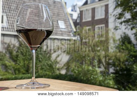 One wineglass with red wine and holland buildings in the day as background