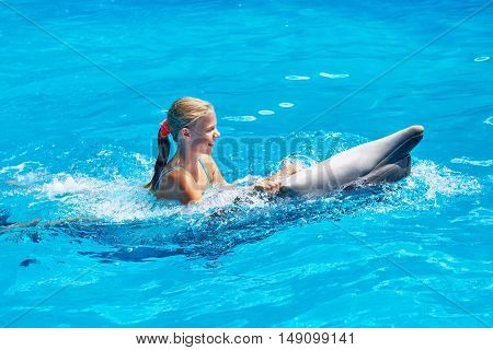 Girl Swims With Dolphin In Pool