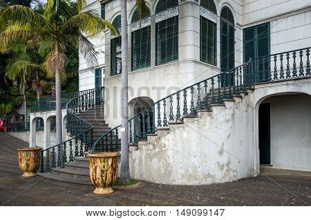 Old white palace entrance with stairs in popular touristic Monte garden, Madeira island, Funchal.