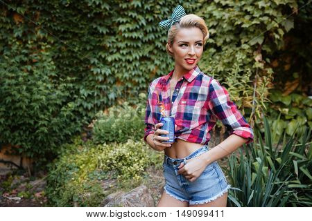 Portrait of happy pretty pin-up girl standing and drinking soda outdoors