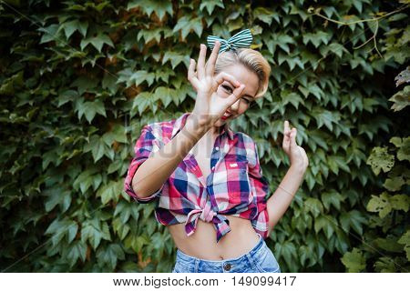 Cheerful pretty pinup girl standing and looking through her fingers in the garden