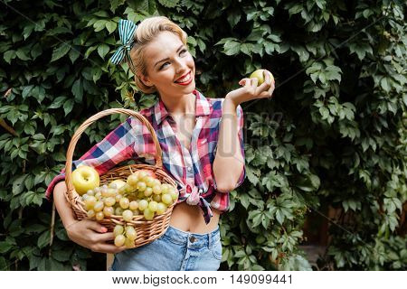 Happy attractive young woman with basket of fruits eating fresh apple