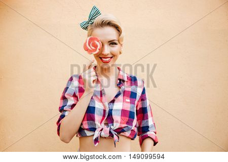 Smiling cute pin up girl covered her eye with lollipop over pink background