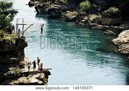 MOSTAR BOSNIA AND HERZEGOVINA - AUGUST 29: People doing high diving into the Neretva river on August 29 2015 in Mostar.