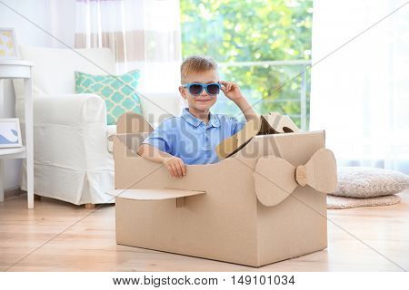 Little boy playing with cardboard airplane indoors