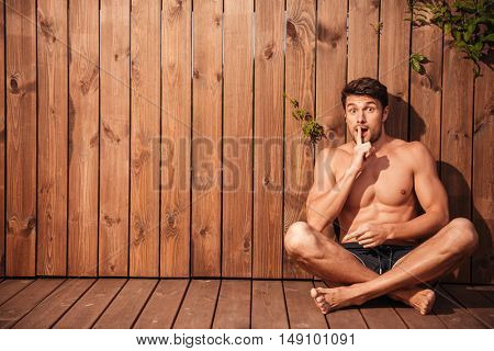 Handsome young excited man sitting and showing silence gesture over wooden background