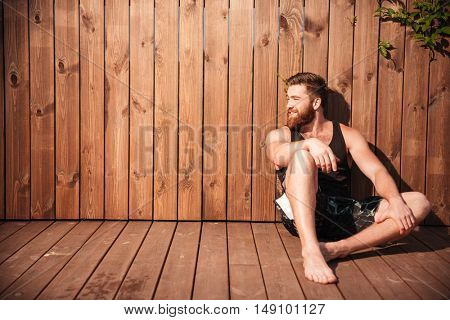 Handsome young smiling bearded man sitting and looking away over wooden background