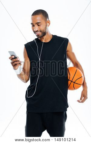 Fitness man using smartphone with headphones holding basket ball isolated on a white background