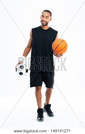 Full length portrait of a smiling african sports man holding basketball and soccer ball isolated on a white background