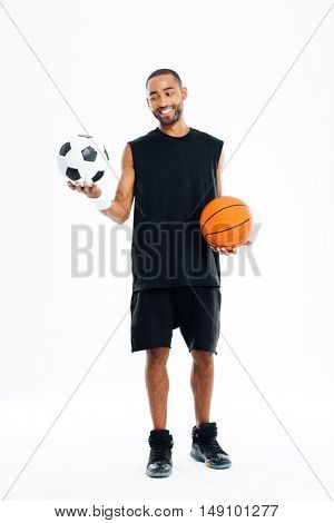 Full length portrait of a smiling african sports man looking at soccer ball isolated on a white background