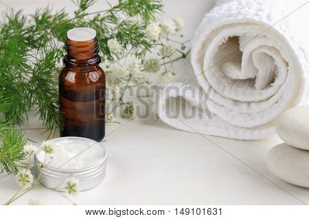 Herbal skincare spa setting. Essential oil, skincare cream, white bathroom towel and stones, fresh herb decor. Place for cosmetic product.