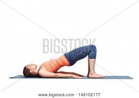 Beautiful sporty fit yogini woman practices yoga asana setu bandhasana - bridge pose beginner variation in studio isolated on white
