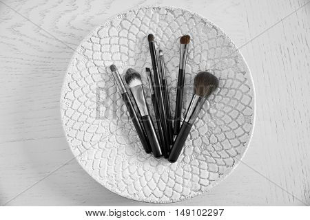 Set of professional makeup brushes on decorative plate, closeup