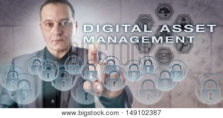 Mature corporate system administrator with concentrated gaze is pressing DIGITAL ASSET MANAGEMENT onscreen. Business concept for information technology management and content management systems.